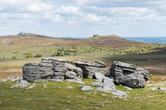 View of the granite bedrock outcrops at Top Tor, Dartmoor National Park, Devon, UK, on a bright cloudy day. To the east across the moorland in the background royalty free stock images