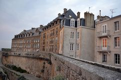 View of granite buildings of Saint-Malo in Brittany, France. View of granite buildings of Saint Malo in Brittany, France. The sunset is reflected on the windows stock photos