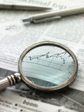View of graph in newspaper through magnifying glass royalty free stock photo