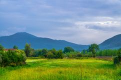 View of grass green field, trees, bushes and Tuscany hills and mountains with beautiful cloudy sky background stock photos