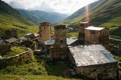 View of grassy field with old weathered rural buildings and hills on background, Ushguli,. Svaneti, georgia royalty free stock photo