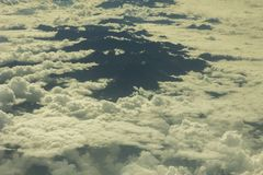 A view from a great height on the protruding black tops of the mountains in white clouds. View from a great height on the protruding black tops of the mountains royalty free stock photography
