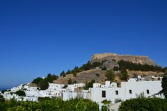 View of the greek Rhodes Islands Old Lindos Town, blue sky, bright colour, white little houses in the hill. Castle on the top Stock Images