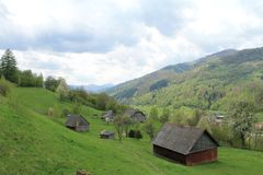 A view of green Carpathian hills with wooden houses. Spring trees and a cloudy sky stock images