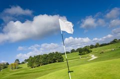 View of a green golf course, hole and flag on a bright sunny day. Sport, relax, recreation and leisure concept. Summer. Landscape with sunbeams Royalty Free Stock Photo