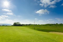 View of a green golf course, hole and flag on a bright sunny day. Sport, relax, recreation and leisure concept. Summer. Landscape with sunbeams Stock Photos