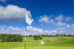 View of a green golf course, hole and flag on a bright sunny day. Sport, relax, recreation and leisure concept. Summer Stock Photos