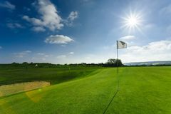 View of a green golf course, hole and flag on a bright sunny day. Sport, relax, recreation and leisure concept. Summer. Landscape with sunbeams Royalty Free Stock Images