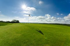 View of a green golf course, hole and flag on a bright sunny day. Sport, relax, recreation and leisure concept. Summer. Landscape with sunbeams Stock Photography