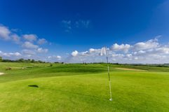 View of a green golf course, hole and flag on a bright sunny day. Sport, relax, recreation and leisure concept. Summer. Landscape with sunbeams Royalty Free Stock Photos