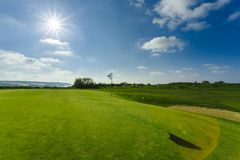 View of a green golf course, hole and flag on a bright sunny day. Sport, relax, recreation and leisure concept. Summer. Landscape with sunbeams Stock Photo