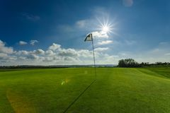 View of a green golf course, hole and flag on a bright sunny day. Sport, relax, recreation and leisure concept. Summer. Landscape with sunbeams Royalty Free Stock Photography
