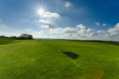 View of a green golf course, hole and flag on a bright sunny day. Sport, relax, recreation and leisure concept. Summer. Landscape with sunbeams Stock Images