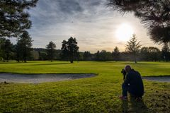 View of green golf course with photographer. At sunset Royalty Free Stock Photography