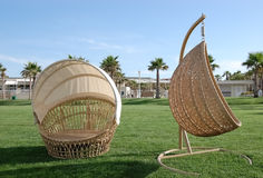 View of a green lawn and wicker hairs-shells for relaxing. Stock Photos