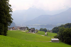 The view on the green meadow with the houses, a lake and the mountains on the background. Royalty Free Stock Photo