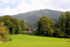 The view on the green meadow with the houses and the mountains on the background. Royalty Free Stock Photos