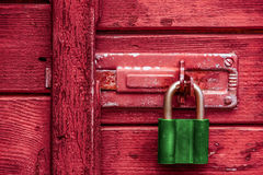 View of green old padlock on the red wooden door. Royalty Free Stock Photos
