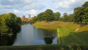 View on a green park in sunny evening in Copenhagen, fake embankment near historic fort. 4K stock footage