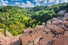 View of a green valley in Sorano over red roofs Stock Photos