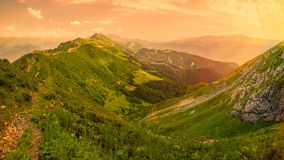 View of the Green Valley, surrounded by high mountains in the light of the sunset yellow sun. Krasnaya Polyana, Sochi, Russia stock photo