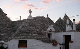 View of group of traditional trulli houses in the Aia Piccola residential area of Alberobello, Puglia Italy. Photographed in early morning stock photography