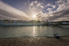 View of Guadalquivir river and Triana district in Sevilla, Andalusia, Spain. People enjoying the sunset stock image