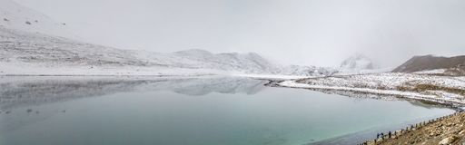 A panoromic view of the Gurudongmar lake with snow covered peaks, Sikkim, India stock photography
