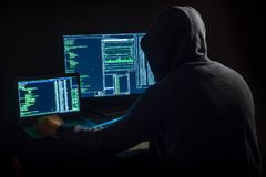 Hacker in front of two monitors with computer code. View of hacker in front of two monitors with computer code stock photography