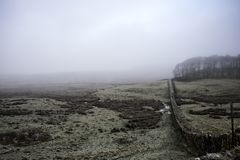 Hadrian`s Wall on a cold, misty day. View of Hadrians wall running into the distant mist royalty free stock photos