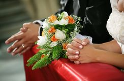 view of the hands of the bride and groom in the church stock photo