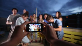 View of hands holding phone and filming happy group of friends dancing stock video