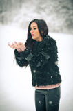 View of happy brunette girl playing with snow in winter landscape. Beautiful young female on winter background. Attractive woman Royalty Free Stock Image