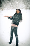 View of happy brunette girl playing with snow in winter landscape. Beautiful young female on winter background. Attractive woman. View of happy brunette girl Royalty Free Stock Photography