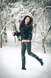 View of happy brunette girl playing with snow in winter landscape. Beautiful young female on winter background. Attractive woman Stock Photography