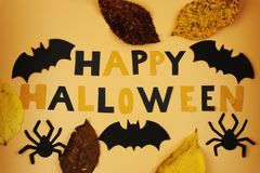 A view on Happy halloween sign with black bats and spiders. Also we can see autumn leaves.Trick or treating. American holiday. stock image