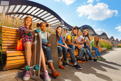 View of happy kids who sit on wooden bench Stock Photo