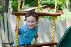 Happy little child boy climbing on the rope ladder outside. View of Happy little child boy climbing on the rope ladder outside Stock Photography