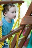 Happy little child boy climbing on the rope ladder outside. View of Happy little child boy climbing on the rope ladder outside Royalty Free Stock Photos