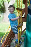Happy little child boy climbing on the rope ladder outside. View of Happy little child boy climbing on the rope ladder outside Stock Photos