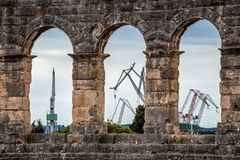 A view on the harbor cranes through the Roman arena in Pula. A view on the harbor cranes through the Roman arena in Pula, Croatia, Europe Royalty Free Stock Photo