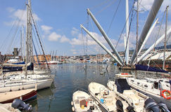 View on harbor of Genoa in Italy. White boats and yachts along piers and modern construction at harbor of Genoa in Liguria, Italy Royalty Free Stock Image