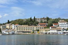 Port of Kassiopi, Corfu. View of the harbour of Kassiopi. Corfu with the castle and fortress on the hill and boats, cafes and hotels by the waterfront royalty free stock image