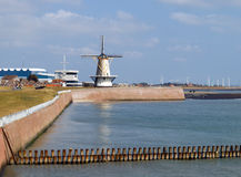 View on a harbour with old and modern windmills. Harbour with old windmill and modern windmills in the background. In the foreground a breakwater, in the Stock Photography