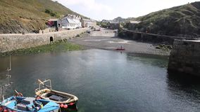 View from the harbour wall to Mullion Cornwall UK situated on Mounts Bay near Helston within Cornish Area outstanding beauty PAN stock video footage