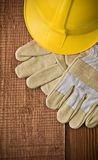 View on a hardhat with gloves on wooden board Stock Photos
