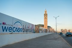 view of Hassan II mosque from the street and billboards showing Wecasablanca Logo Royalty Free Stock Photography