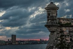 View of Havana Cuba from Morro Castle. View from across the water at Morro Castle to Havana Cuba of the wild colors of the sun setting stock images
