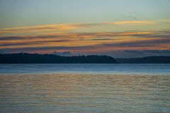 Hazy Northwest Sunset. A view of a hazy sunset with a fence from West Seattle, Washington royalty free stock image