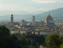 View of the heart of Florence: cathedral Santa Maria del Fiore and tower of Palazzo Vecchio taken from the other bank of the Arno. River. Soft golden light of royalty free stock photography